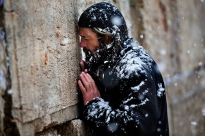Snow falls a an ultra-orthodox Jewish man prays at the Western Wall in Jerusalem's Old City, Thursday, Jan. 10, 2013. Stormy weather conditions continued on Thursday with snow, torrential rains and strong winds across the region. (AP Photo/Bernat Armangue)